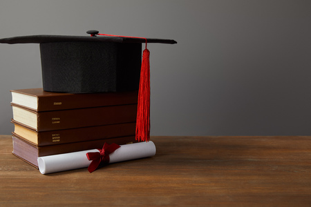 Diploma, academic cap and books on wooden surface on grey Фото со стока - 120210853