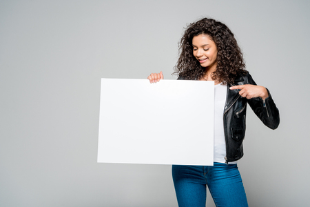 cheerful african american young woman pointing with finger at blank placard while standing isolated on grey