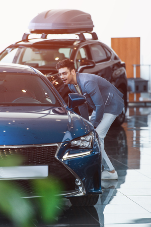 cheerful stylish man in glasses standing near automobile in car showroom