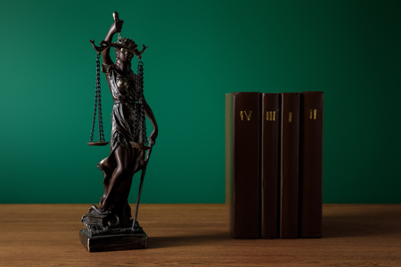 bronze statuette with scales of justice and volumes of brown books on wooden table on dark green background
