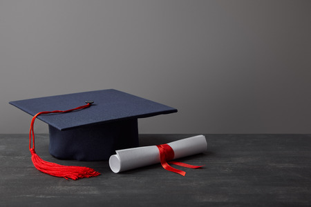 Diploma and academic cap with red tassel on dark surface on grey