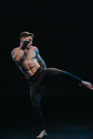 muscular shirtless and barefoot mma fighter in bandages doing kick isolated on black
