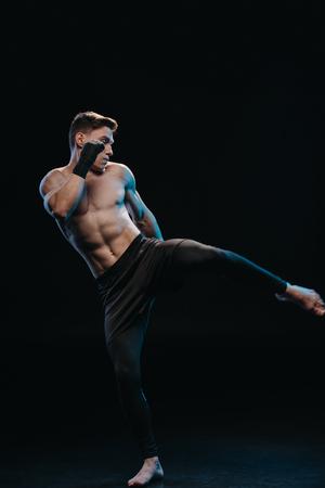 muskularny, bez koszuli i boso wojownik mma w bandażach, wykonujący kopnięcie izolowane na czarno Zdjęcie Seryjne