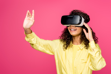 happy curly african american woman wearing virtual reality headset and gesturing isolated on crimson