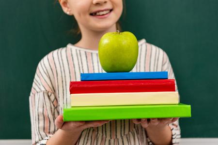 Ausgeschnittene Ansicht eines fröhlichen Ingwer-Schulmädchens, das Bücher und grünen Apfel vor der Tafel im Klassenzimmer hält holding