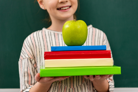Cropped view of cheerful ginger shoolgirl holding books and green apple in front of blackboard in classroom