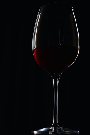 Glass of burgundy red wine isolated on black Stock Photo