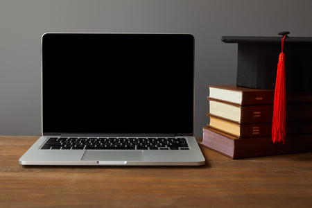 Laptop with blank screen, books and academic cap on wooden surface isolated on grey