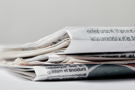 selective focus of newspapers with lettering on grey