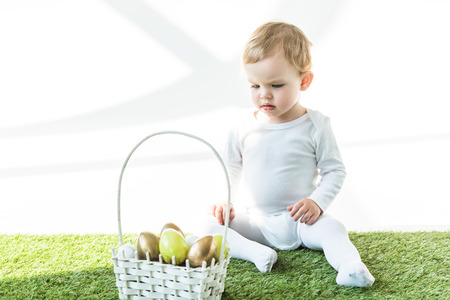 adorable child sitting on green grass near straw basket with yellow and golden Ester eggs isolated on white