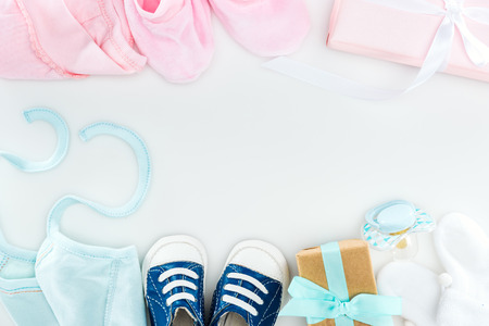 top view of booties and sneakers, pacifier, gift boxes and bonnets on white background