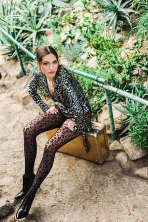 Dreamy sexy woman in black pantyhose sitting on suitcase in botanical garden 스톡 콘텐츠