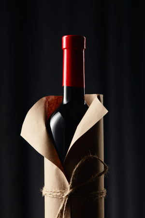Glass wine bottle in paper wrapper on dark