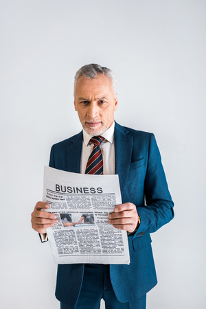 mature man in formal wear holding business newspaper while standing isolated on grey 스톡 콘텐츠