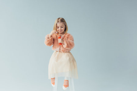 adorable kid in faux fur coat and skirt sitting on highchair and holding bottle with soap bubbles isolated on grey