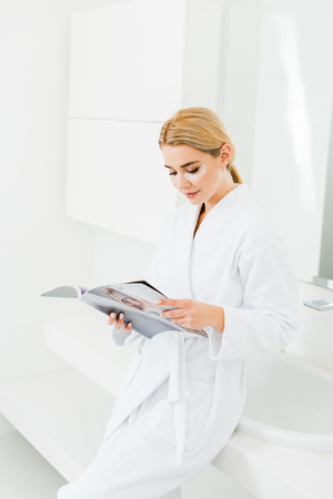 beautiful and blonde woman in white bathrobe with eye patches on face reading magazine