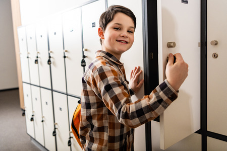 Smiling schoolboy in checkered shirt with backpack opening locker 스톡 콘텐츠