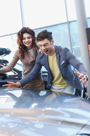 selective focus of excited man in glasses looking at car near beautiful curly woman in car showroom