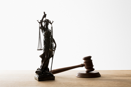 bronze statuette with scales of justice near wooden gavel on table isolated on white