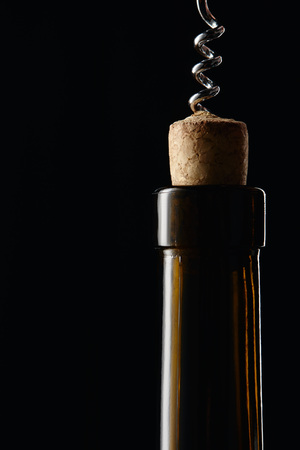Glass wine bottle with wooden cork and corkscrew isolated on black