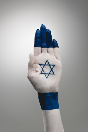 cropped view of female hand with star of david on grey