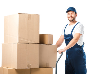 handsome mover in uniform looking at camera while transporting cardboard boxes on hand truck isolated on white