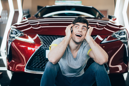 selective focus of excited man sitting near new red luxurious car