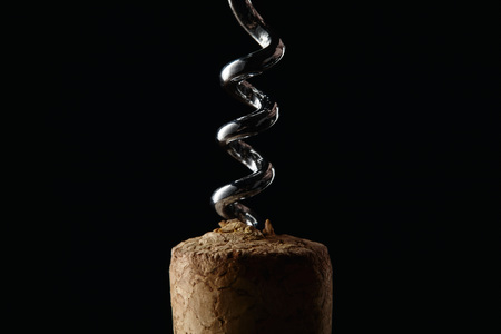 Close up view of wooden cork and steel corkscrew isolated on black 스톡 콘텐츠