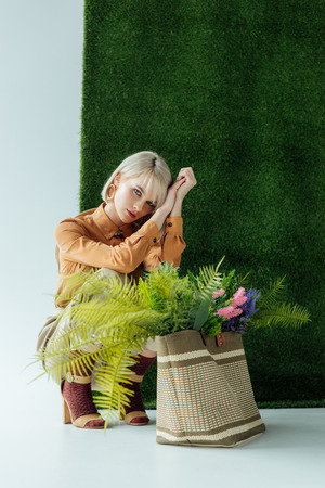 beautiful fashionable girl posing near bag with fern and flowers on white with green grass