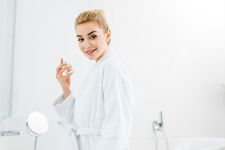 beautiful and smiling woman in bathrobe holding perfume and looking at camera