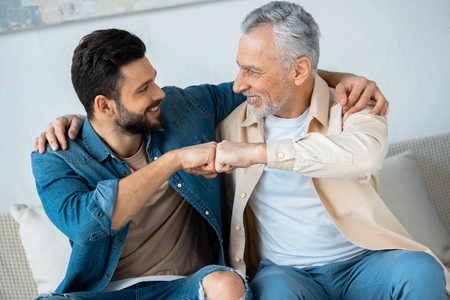 cheerful retired man fist bumping with happy bearded son at home