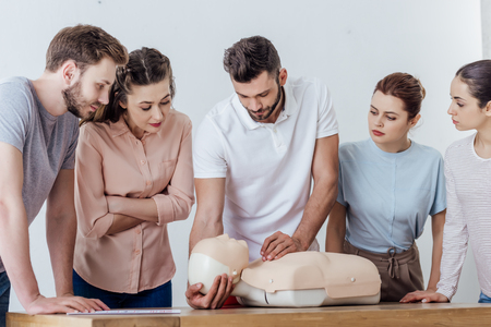 group of concentrated people with cpr dummy during first aid training class Stock Photo