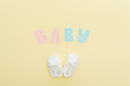top view of booties and baby lettering isolated on yellow