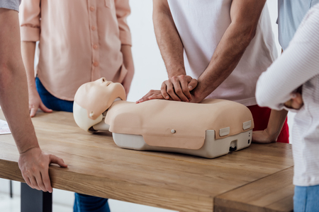 cropped view of man performing chest compression on dummy during cpr training class Stock Photo