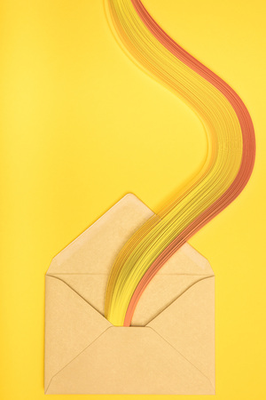 top view of open yellow envelope with rainbow on yellow background