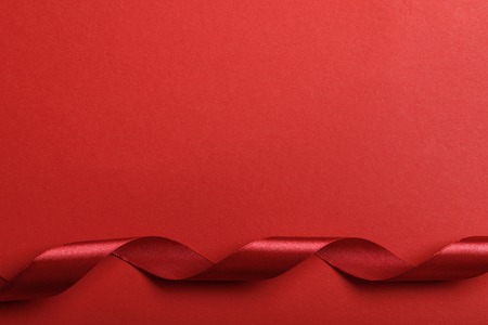 top view of curved silk red ribbon on red background