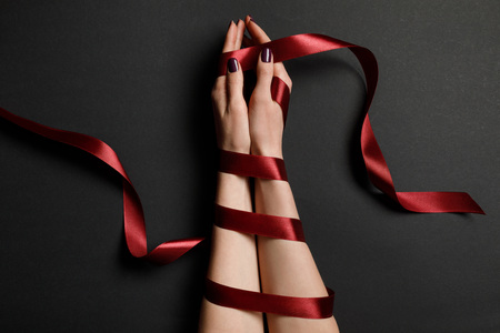 partial view of female hands in silk red ribbon on black background Stock Photo