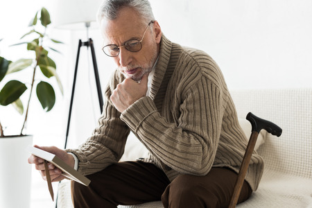 pensive retired man holding photo frame while sitting on sofa near walking stick Stock Photo