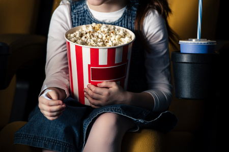 partial view of child holding paper cup with popcorn in cinema