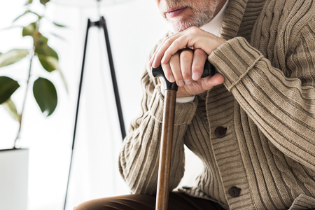 cropped view of retired man holding walking stick