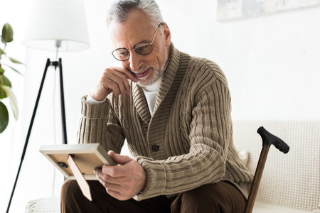cheerful retired man holding photo frame while sitting on sofa near walking stick Stock Photo