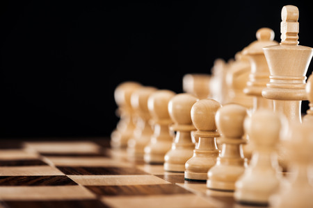 selective focus of wooden chessboard with beige chess figures isolated on black