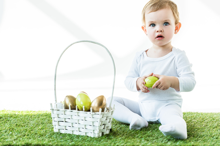 cute blonde baby holding yellow chicken egg while sitting on green grass near straw basket with Easter eggs isolated on white