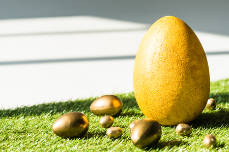 yellow ostrich egg and golden Easter eggs on green grass surface 写真素材