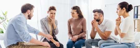 panoramic shot of group of people sitting on chairs during therapy session
