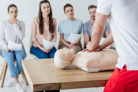 back view of instructor performing cpr on dummy during first aid training with group of people Banco de Imagens