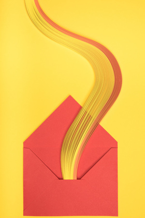 top view of open red envelope with rainbow on yellow background 版權商用圖片