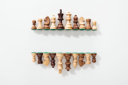 top view of rows made of wooden chess figures on white background with copy space