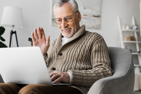 cheerful senior man in glasses waving hand while having video call