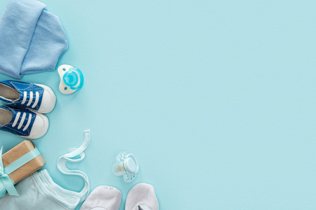 top view of pacifiers, gift, sneakers, bonnet, booties, hat on blue background with copy space